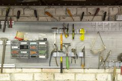 Old tools hanging on wall in metalwork workshop , Tool shelf aga. Inst a wall stock images