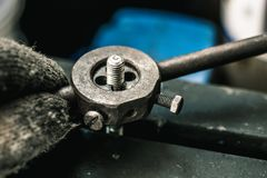 Old tools ,Mechanic using Taps and Dies tool Making Internal and External Threads nut at motorcycle garage .selective focus.  royalty free stock photo