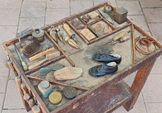 Old tools of the shoemaker. Work table with small shoes for children and old tools of the artisan shoemaker for repair and finishing shoe royalty free stock photo
