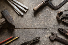 Old tools on the table, copyspace. Old tools on the old workshop, wooden table, hummer, measure, saw, wrench, plies, pencils Stock Images