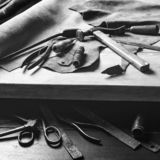 Old tools at table. Pieces of leather at cobbler workplace. Shoemaker`s work desk. Leather craft tools on wooden background. Shoe stock image