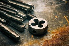 Old tools ,Taps and Dies, Cutting Tools for hand or machine tapping of through or blind holes on rusty metal plate background at. Motorcycle garage stock photography