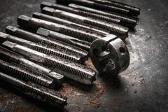 Old tools ,Taps and Dies, Cutting Tools for hand or machine tapping of through or blind holes on rusty metal plate background at. Motorcycle garage royalty free stock photography