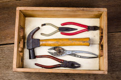 Old tools with tool box. Old carpenter tools in toolbox on wooden board background,rust pliers stock photo