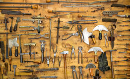Old tools on the wall. Various old tools on the wall in leather craft workshop royalty free stock photo
