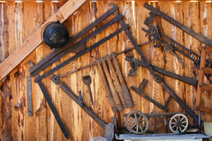 Old tools in wood shed. Old tools hanging on the wall in wood shed - grunge background stock photo