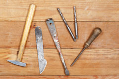 Old tools on wooden boards. Hammer, knife, screwdriver, file, drill. Stock Images
