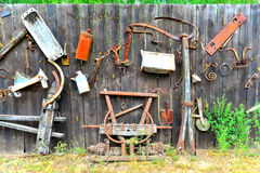 Old tools on a wooden fence. Different old tools and vehicle parts on an old wooden fence royalty free stock photography