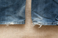 Old torn jeans on a background of burlap. Royalty Free Stock Images
