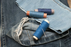 Old torn jeans on a background of burlap. Stock Images