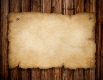 Old torn paper on grunge wooden wall. Old torn paper pinned by nails to grunge wooden wall stock photo