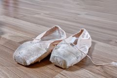Old torn Pointe on a wooden surface, unfit for use stock image