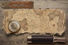 Old torn treasure map with compass and spyglass. Adventure and travel concept. 3d illustration. stock image