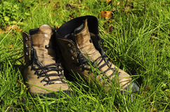 Old touristic shoes on a grass. Selective focus Royalty Free Stock Images