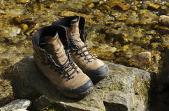 Old touristic shoes in a river. Selective focus Royalty Free Stock Photography