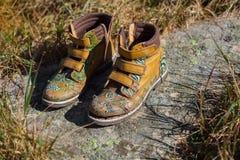 Old tourists boots on stone near mountain stream Stock Photos