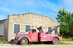Old Tow Truck. An aged tow truck parked in front of an old garage Stock Images