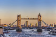 Tower Bridge in London at night or sunset. Old Tower Bridge in London at night or sunset over the river Thames with yellow light behind Royalty Free Stock Photography