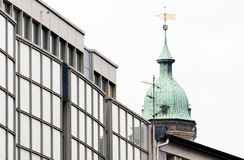 Old tower of a church behind the ugly glass façade of a new building. In Germany royalty free stock photography