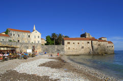 Old Town beach,Budva,Montenegro. Tourist relaxing at beach restaurant tables on Adriatic sea by the walls of Old Town of Budva .Budva is notable for its long Stock Photography