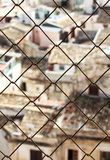 Old town, blurred, through a wire mesh Stock Photo