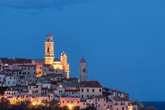 The old town of Cervo, Liguria, Italy, with the beautiful baroque church arising from the houses. Clear blue sky. Stock Photos