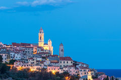 The old town of Cervo, Liguria, Italy, with the beautiful baroque church and tower bells arising from the colorful houses, illumin. Ated at twilight Royalty Free Stock Photo