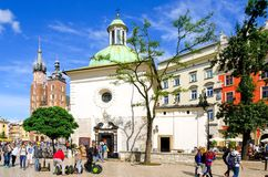 Old town in Cracow, Poland. CRACOW, POLAND - AUGUST 16, 2014: Tourists visiting the main market square in Cracow (Poland), which is one of the most famous and stock images
