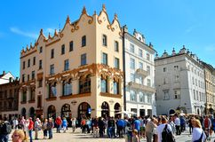 Old town in Cracow, Poland. CRACOW, POLAND - AUGUST 16, 2014: Tourists visiting the main market square in Cracow (Poland), which is one of the most famous and stock image