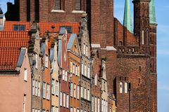 Old Town of Gdansk Historical Architecture. City of Gdansk in Poland, historical tenement houses with gables against monumental brick structure of the St. Mary`s Stock Photos
