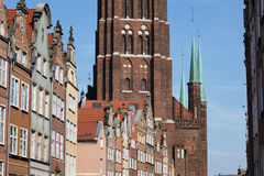 Old Town of Gdansk in Poland. City of Gdansk in Poland, historical tenement houses, apartment buildings with gables against massive brick structure of the St Stock Photos