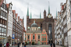 Old Town in Gdansk. Gdansk, Poland - 17th October 2014: People at Grobla Street with King's Chapel on foreground and Basilica of the Assumption of the Blessed Royalty Free Stock Photography