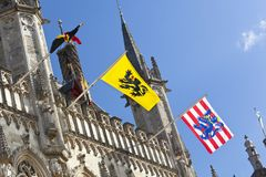 Town Hall Of Bruges. The old town hall of Bruges with blue sky and the waving flags of Belgium, Flanders and Bruges Stock Photo
