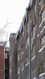 The old town house with icicles. Part of the old building, view from the courtyard. Wall of gray building, with a roof hanging icicles. The plaster has fallen royalty free stock photos