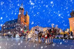 Old town of Krakow on a cold winter night with falling snow. Poland royalty free stock photo