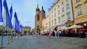 In Old Town of Krakow, Poland. KRAKOW, POLAND - JUNE 10, 2018: People walk in Main Square Plac Mariacki of Old Town Stare Miasto with a view on restaurants stock video footage