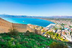 Old town of Nafplion in Greece. View from above with tiled roofs, small port and bourtzi castle on the Mediterranean sea water Stock Photos