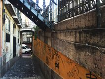 Old town. Old narrow street in downtown Lisbon. both sides with graffiti and a metalic stair over Stock Images