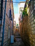 Old town narrow street with stairs, doors, windows and flower garlands Croatia royalty free stock photography