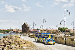Old town of Nessebar, Bulgaria. Tourist train in front of the symbol of Nessebar - the old wooden windmill Stock Photos