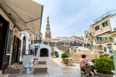 Old town in Ostuni, Italy. OSTUNI, ITALY - MAY 16, 2015: tourists visit old town and Statue of San Oronzo in Ostuni, Italy. Ostuni is one of the most beautiful Royalty Free Stock Photography