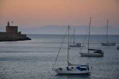 Old Town of Rhodos while pink sunset, calm sea, greek monument and harbour view. Warm colours, foggy background. Rhodos, Greece, E royalty free stock photos