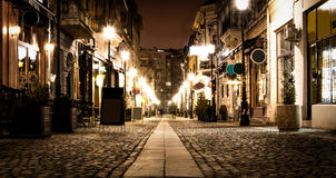 Old City Bucharest. An old city center pedestrian street with causeway, lighting poles,  and restaurants in old buildings with food menu by the entrance Stock Image