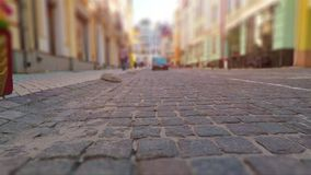 Old town street in retro colors. Creative abstract urban architecture retro background: old town street with stone pavement, blurred cars and pedestrians in stock video footage