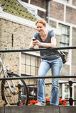 Old Town Street - Woman with Phone Royalty Free Stock Image