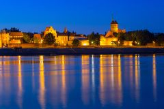 Old town of Torun at night reflected in Vistula river stock photography