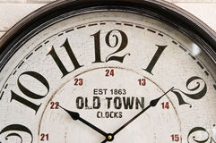 Old town wall clock face. A classic clock face on white wall stock photo