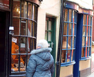 Old town, Whitby, North Yorkshire. A senior lady browsing the shops in the old town of Whitby, North Yorkshire, England, UK Royalty Free Stock Images