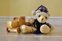 Old toy bear with a wooden car Stock Photos