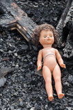Old toy doll in the midst of ruins and devastation.  Stock Photo